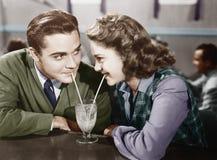 Couples dans un restaurant regardant l'un l'autre et partageant un lait de poule avec deux pailles (toutes les personnes représen Image stock