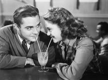 Couples dans un restaurant regardant l'un l'autre et partageant un lait de poule avec deux pailles (toutes les personnes représen Image libre de droits