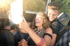 Couples dans une voiture au coucher du soleil Photographie stock
