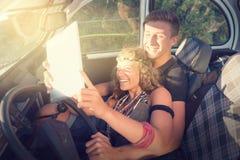 Couples dans une voiture au coucher du soleil Photographie stock libre de droits