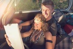 Couples dans une voiture au coucher du soleil Images stock