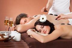 Couples décontractés recevant la thérapie en pierre chaude à la station thermale Image stock