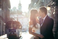 Couples de baiser adorables de nouveaux mariés au fond de la vieille ville pendant le coucher du soleil Images libres de droits