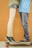 Couples de baiser de plan rapproché à la planche à roulettes et au fond rouge de mur Images stock