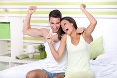 Couples de bonheur regardant dans l'essai de grossesse se reposant sur le lit Image stock