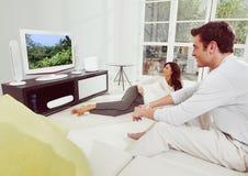 Couples de bonheur regardant la TV Photos libres de droits