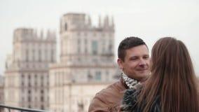 Couples de brune dans l'amour sur un toit d'une maison L'homme bel regarde le sien aimé Vue brouillée de fond d'une ville clips vidéos