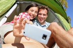 Couples de camping dans la tente prenant le smartphone de selfie Images stock