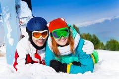 Couples de caresse dans des masques de ski se trouvant sur la neige Photos stock