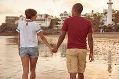 Couples de causerie flânant sur la plage Photographie stock libre de droits