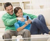 Couples de chemin mélangé regardant un téléphone portable ensemble Photos libres de droits
