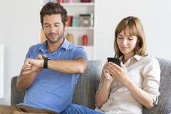 Couples de connaisseur de Digital Téléphone portable, montre intelligente Appartement blanc moderne Photos libres de droits