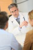 Couples de consultation de docteur dans le bureau d'hôpital Images stock
