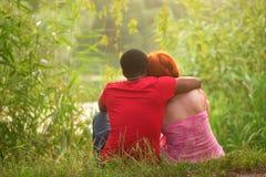 Couples de course de mélange détendant par la rivière Images stock