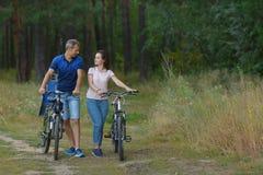 Couples de cycliste dans la forêt de pin, promenade romantique Photos libres de droits