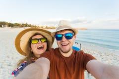 Couples de déplacement heureux dans l'amour prenant un selfie au téléphone à la plage un jour ensoleillé d'été Jolie fille et ell Photos stock