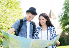 Couples de déplacement recherchant leur prochaine destination avec une carte Images stock