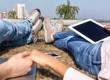 Couples de datation détendant sur la pelouse dans la ville moderne Photos libres de droits