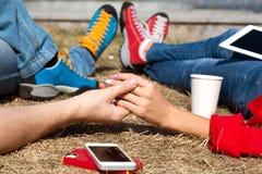 Couples de datation détendant sur la pelouse dans la ville moderne Photographie stock libre de droits
