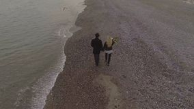 Couples de datation marchant sur le bord de la mer tenant des mains, fleurs de transport de fille, date banque de vidéos