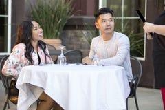 Couples de datation passant commande à un restaurant extérieur image stock
