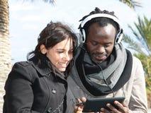 Couples de différentes courses appréciant de nouvelles technologies Photographie stock libre de droits