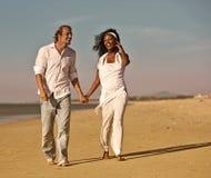 Couples de diversité marchant et fonctionnant sur la plage Photo stock