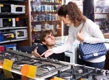 Couples de famille achetant la nouvelle cuisinière à gaz Photographie stock libre de droits