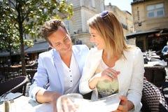 Couples de fantaisie mangeant dans le restaurant dehors Photos libres de droits