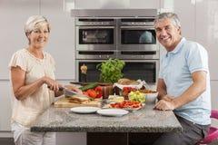 Couples de femme d'homme effectuant des sandwichs dans la cuisine images libres de droits