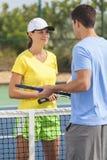 Couples de femme d'homme jouant le tennis ou la leçon Photographie stock