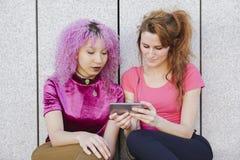 Couples de femme de l'adolescence partageant des écouteurs et écoutant la musique dessus Photo stock