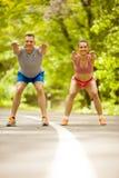 Couples de forme physique s'étendant dehors en parc Photographie stock libre de droits