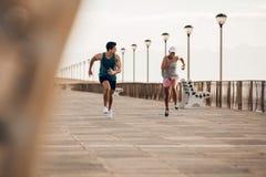 Couples de forme physique sprintant sur la promenade Photographie stock