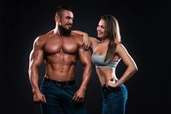 Couples de forme physique sur un fond noir se regardant et le sourire photo libre de droits