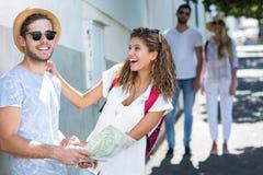 Couples de hanche tenant la carte et rire Image libre de droits