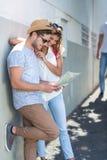 Couples de hanche vérifiant la carte et se penchant contre le mur Photographie stock