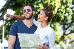 Couples de hanche vérifiant la carte et se dirigeant quelque part Photos libres de droits