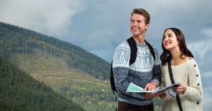 Couples de hausse réfléchis tenant la carte sur la montagne Photos libres de droits