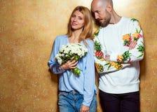 Couples de hippie dans l'amour avec un bouquet des fleurs dans le studio, Photographie stock