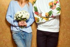 Couples de hippie dans l'amour avec un bouquet des fleurs dans le studio, Images libres de droits