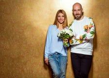 Couples de hippie dans l'amour avec un bouquet des fleurs dans le studio, Photos stock