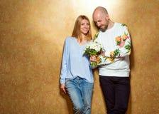 Couples de hippie dans l'amour avec un bouquet des fleurs dans le studio, Photo libre de droits