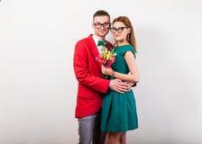 Couples de hippie dans l'amour avec un bouquet des fleurs dans le studio a Photographie stock
