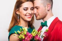 Couples de hippie dans l'amour avec un bouquet des fleurs dans le studio a Photographie stock libre de droits