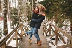 Couples de hippie de cheveux bouclés étreignant dans la forêt d'hiver Photographie stock