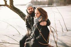 Couples de hippie se reposant sur l'arbre au-dessus du lac congelé Photographie stock libre de droits