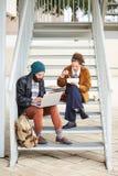 Couples de hippie utilisant l'ordinateur et de consommation le déjeuner dehors Photo libre de droits