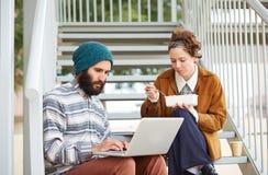 Couples de hippie utilisant l'ordinateur et de consommation le déjeuner dehors Photo stock