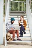 Couples de hippie utilisant l'ordinateur et de consommation le déjeuner dehors Images libres de droits
